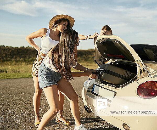 Freundinnen holen Koffer aus dem Kofferraum eines Autos Freundinnen holen Koffer aus dem Kofferraum eines Autos