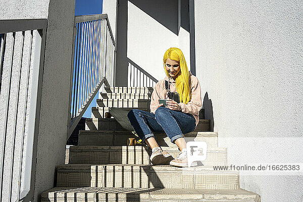 Young woman using smart phone while sitting on steps