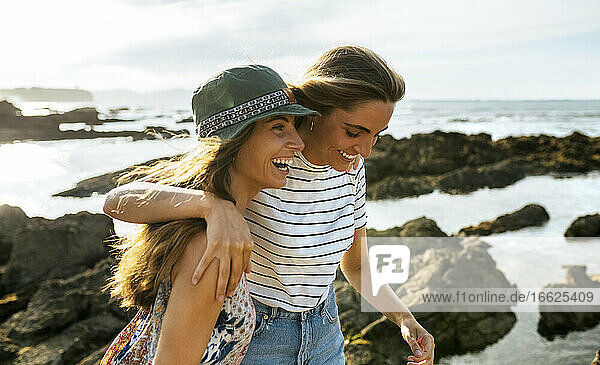 Cheerful young sisters enjoying at beach during weekend