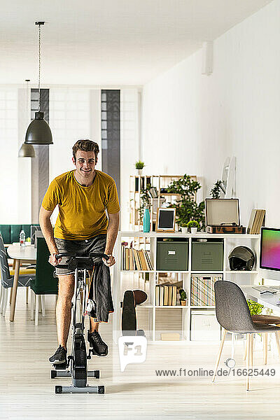 Smiling young man cycling on exercise equipment at home