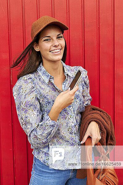 Lächelnde Frau  die ihre Jacke und ihre Handtasche hält  während sie ein Mobiltelefon gegen eine rote Metalltür hält Lächelnde Frau, die ihre Jacke und ihre Handtasche hält, während sie ein Mobiltelefon gegen eine rote Metalltür hält
