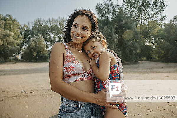 Mother and daughter embracing while standing at beach