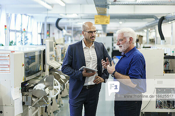Businessman holding digital tablet while looking at senior manager discussing at illuminated factory
