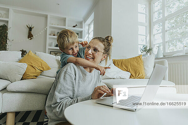 Boy pointing at laptop while standing behind mother at home