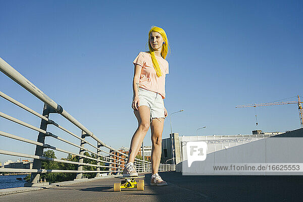 Woman standing on skateboard against clear during sunny day