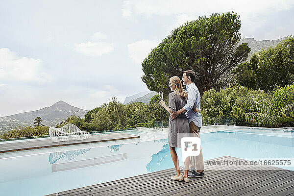 Heterosexual couple looking at view with wine glass standing near pool