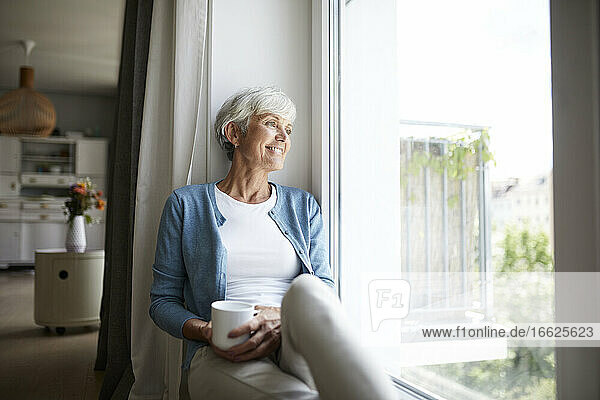 Senior woman looking out of window while sitting at home