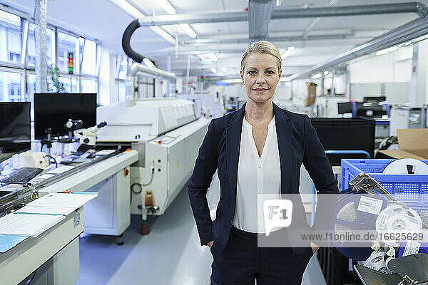 Confident female professional standing with hands in pockets in illuminated factory