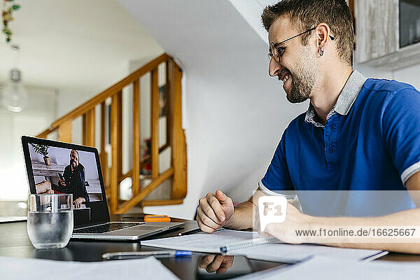 Smiling man consulting professor through video call from laptop at home