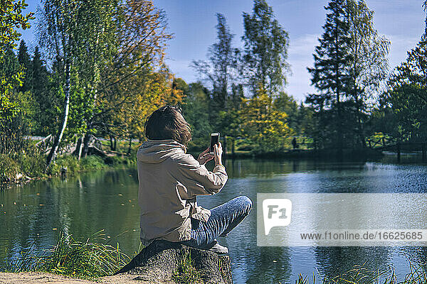 Woman photographing through smart phone while sitting at lakeshore