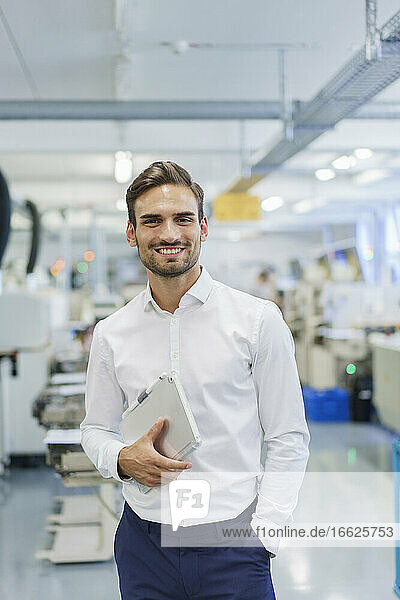 Smiling young businessman holding digital tablet while standing with hands in pockets at illuminated factory