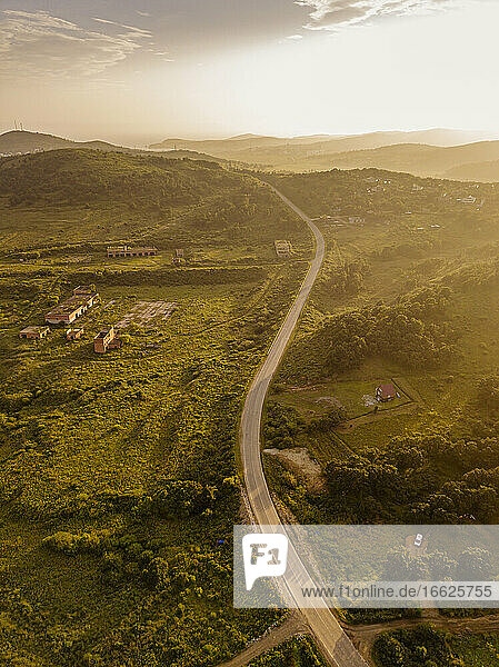 Russia  Primorsky Krai  Zarubino  Aerial view of road stretching along hilly landscape at sunset