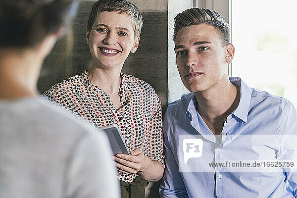 Colleagues looking at businesswoman while standing in office