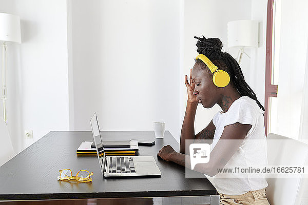Junge Frau mit Kopfhörern und geschlossenen Augen sitzt am Schreibtisch im Home Office Junge Frau mit Kopfhörern und geschlossenen Augen sitzt am Schreibtisch im Home Office