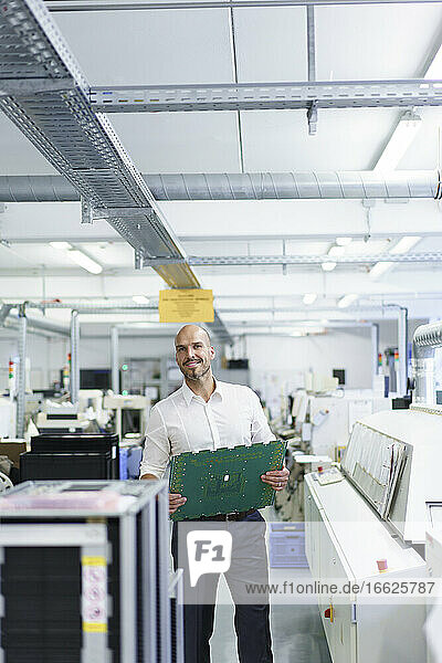 Smiling male technician holding large circuit board by machinery at factory