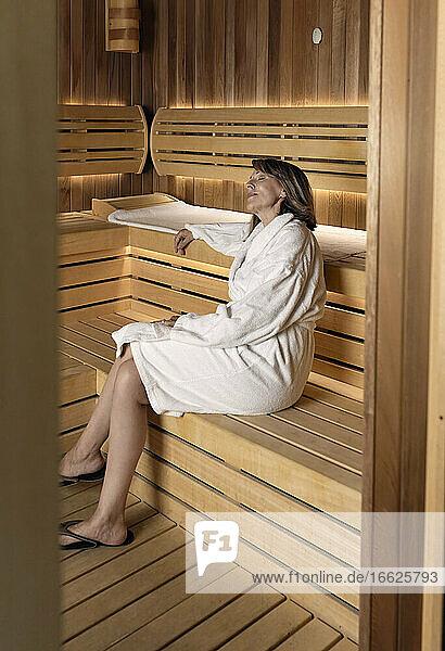 Thoughtful woman wearing bathrobe sitting on wooden sauna at health spa