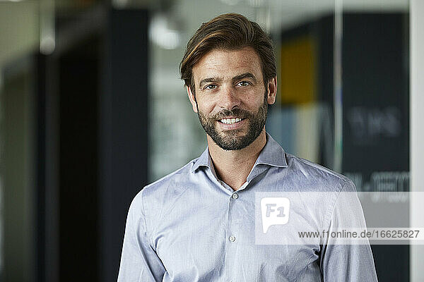 Smiling businessman standing against glass wall in office