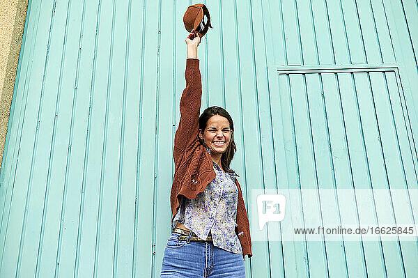 Glückliche Frau mit erhobener Hand  die die Mütze hochhält  während sie vor einer blauen Metalltür steht Glückliche Frau mit erhobener Hand, die die Mütze hochhält, während sie vor einer blauen Metalltür steht