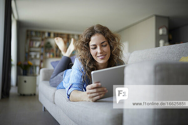Woman using digital tablet while lying on sofa at home