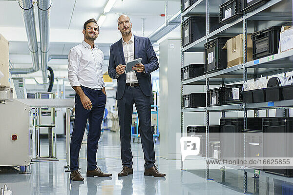 Businessman holding digital tablet while standing by smiling engineer and looking away at factory