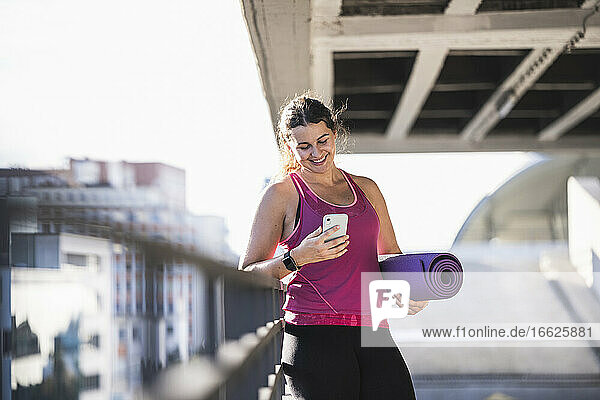Smiling young woman holding exercise mat using smart phone while standing by railing