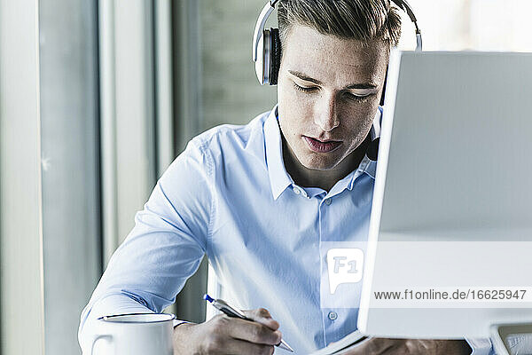 Close-up of male customer representative wearing headset while working in call center