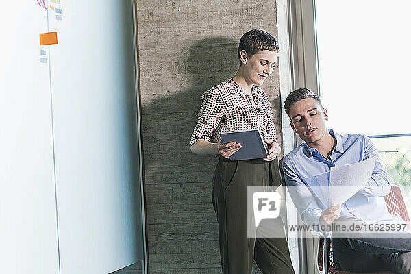 Businessman showing reports to female coworker while discussing with her in office
