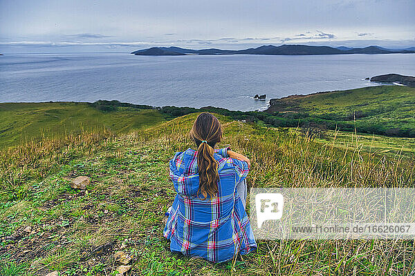 Woman looking at sea of Japan while sitting on mountain  Krabbe Peninsula  Primorsky Krai  Russia
