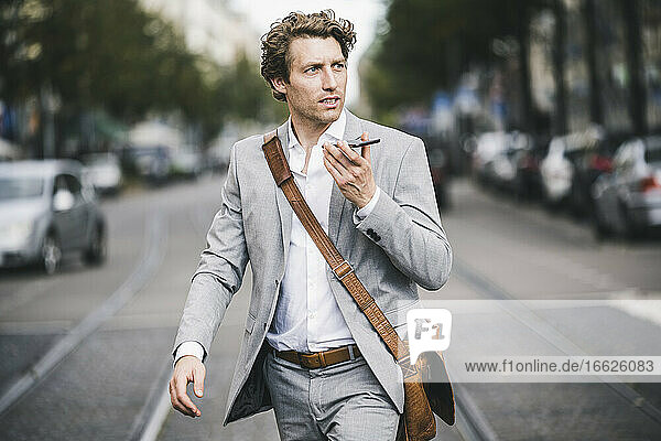 Man with bag talking on phone while walking at tramway in city