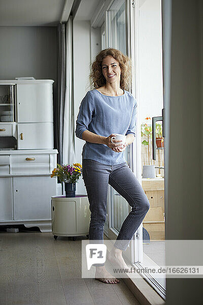 Smiling woman holding coffee cup while leaning on door by balcony at home