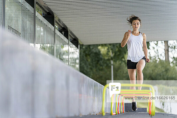 Serious female athlete running over small hurdles