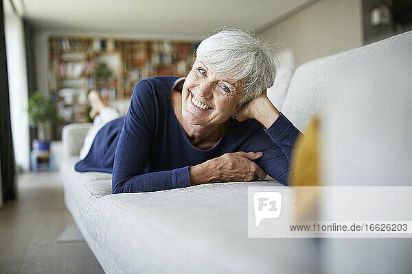 Smiling senior woman with head in hand lying on sofa at home