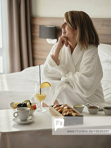 Smiling thoughtful senior woman looking away while sitting with breakfast in luxury hotel room