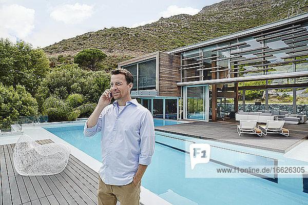 Älterer Mann  der mit den Händen in den Taschen vor einem modernen Haus steht und telefoniert Älterer Mann, der mit den Händen in den Taschen vor einem modernen Haus steht und telefoniert