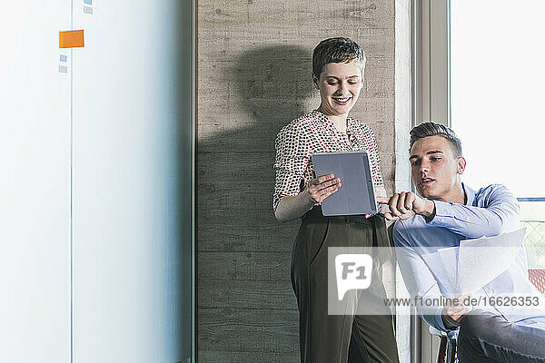 Businessman discussing over digital tablet with female coworker in office