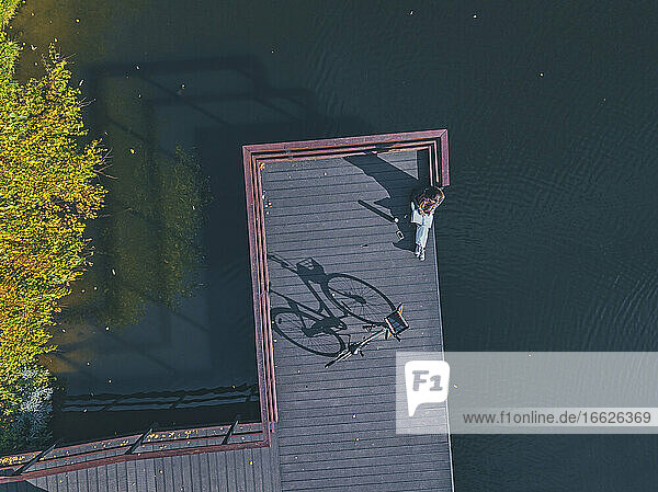 Aerial view of young woman reading book at edge of coastal jetty