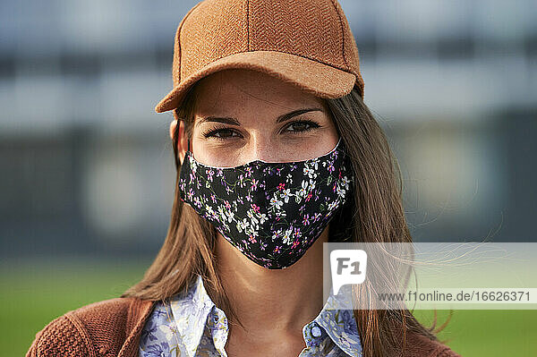 Young woman wearing cap and face mask standing in city