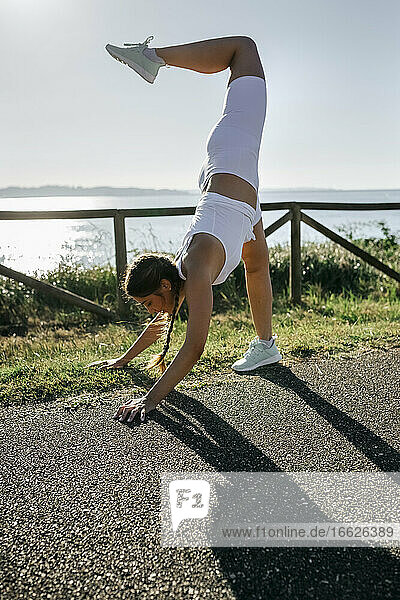 Young woman practicing handstand on road against sea during sunset