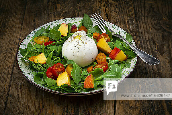 Plate of fresh vegetarian salad with tomatoes  basil  arugula  nectarines  lemon balm andburratacheese