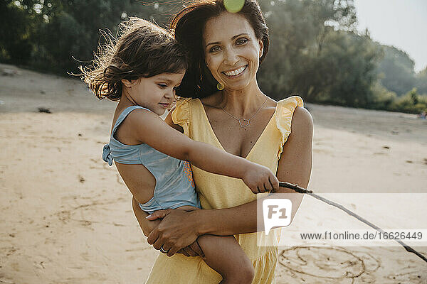 Smiling mother holding daughter in arms while standing at beach