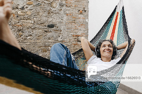Smiling woman listening music through headphones while relaxing on hammock against wall at back yard