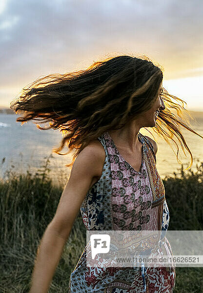 Cheerful young woman tossing hair against sky during sunset