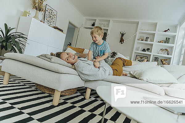 Smiling mother and boy playing on sofa at home