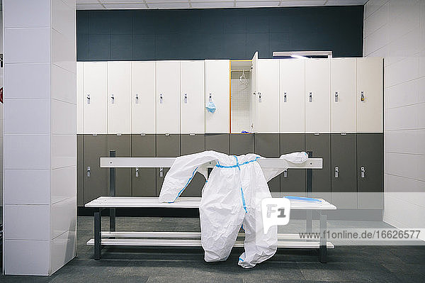 Protective wear and face shield kept on bench in locker room at hospital