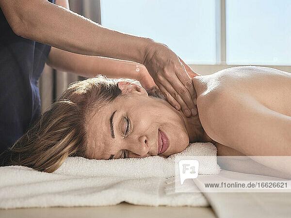 Midsection einer Frau bei der Massage einer älteren Frau im Spa Midsection einer Frau bei der Massage einer älteren Frau im Spa