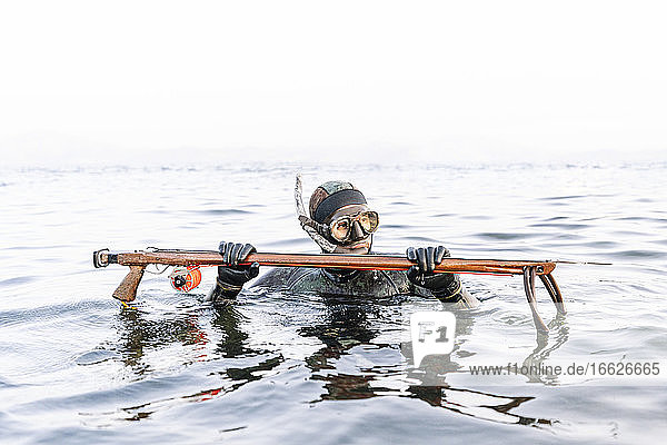 Man hunting with harpoon in sea against clear sky