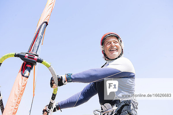 Cheerful senior man windsurfing against clear sky during sunny day