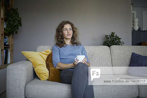 Smiling with coffee cup woman looking away while sitting on sofa at home