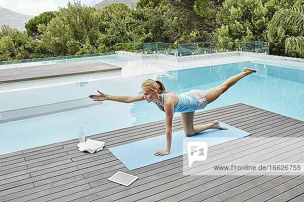 Young woman practicing yoga near swimming pool
