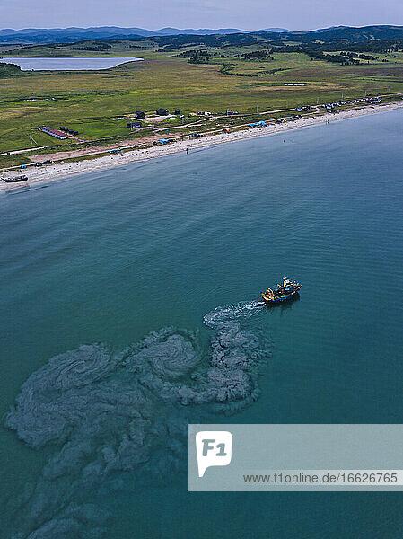 Aerial view of trawler fishing near coast in Lukin bay